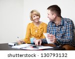Happy young couple paying bills at home. - stock photo