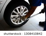 Small photo of bright light of day and a mechanic in blue uniform with white glove holding a pound wrench tighten the bolts of the wheel