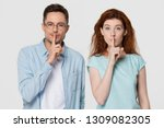 Small photo of Young mute couple holding fingers on lips mouth to keep it quiet hush secret showing shh shush gesture for conspiracy silence looking at camera isolated on white grey blank studio background