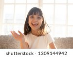 Small photo of Happy cute little vlogger waving hand saying hello hi looking at camera talking to webcam, smiling kid child girl making online video call recording vlog sitting on sofa at home, portrait