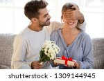 Small photo of Loving man husband boyfriend with flowers closing eyes of woman girlfriend holding gift box guessing present making romantic surprise to wife, couple celebrating Valentines day anniversary birthday