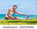 Small photo of Fitness woman stretch legs doing warm-up before run workout training outdoor. Asian athlete stretching side hamstring muscle yoga stretched leg stretches exercises in outdoor gym.