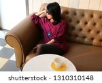 woman sitting on a sofa with an ... | Shutterstock . vector #1310310148