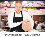 Shopkeeper showing a bologna in an italian grocery store - stock photo