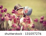 Two kissing vintage style dolls in tulip garden. - stock photo