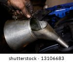 Greasy hand pouring motor oil into a car engine - stock photo