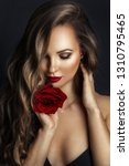 Stock photo fashion portrait of young beautiful lady with red rose on black background 1310795465