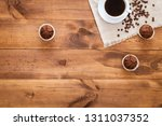 Stock photo cup of black coffee muffins and coffe beans scattered on brown wooden table cofee cafe cafeteria 1311037352