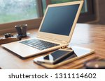 glasses and laptop on the table ... | Shutterstock . vector #1311114602