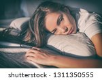 tired woman lying in bed can't... | Shutterstock . vector #1311350555