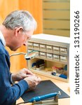 Small photo of hearing aid acoustician at work, he is working on a hearing aid for hearing impaired persons