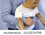 Small photo of Abdominal thrusts (the Heimlich maneuver or Heimlich manoeuvre) on a simulation mannequin child dummy during medical training Basic Life Support