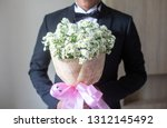 the groom is holding a bouquet... | Shutterstock . vector #1312145492