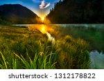 lake awaking in sunlight trough ...   Shutterstock . vector #1312178822