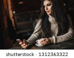 woman using phone and drinking... | Shutterstock . vector #1312363322