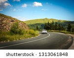 a car on a mountain road in... | Shutterstock . vector #1313061848