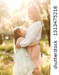 mother hugging her daughter in... | Shutterstock . vector #1313475218