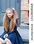schoolgirl at the door of the... | Shutterstock . vector #1313808068