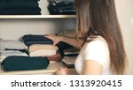 housewife organizing clothes in ... | Shutterstock . vector #1313920415