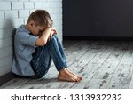 a young boy sits alone with a... | Shutterstock . vector #1313932232