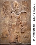 Small photo of Assyrian wall relief of a winged genius. Ancient carving panel from the Middle East history. Remains of the culture of ancient Assyrian and Sumerian civilization. Art of Mesopotamia.