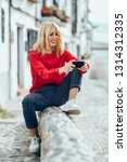 happy young blond woman sitting ... | Shutterstock . vector #1314312335