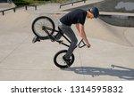 Small photo of Toronto, Ontario, Canada - May 23, 2009: Flatland BMX rider doing a Nose Manual Dork Wheelie trick on front wheel