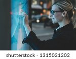 Small photo of Smiling female standing at big display with advanced digital technology. Young woman touching with finger sensitive screen of interactive kiosk for find information while standing on street in evening