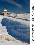 Small photo of Snow drift off highway 32 at Pillsbury Mills Grain Elevator in Idaho in winter with Teton Range mountains