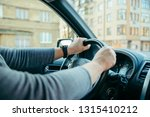 man driving car by city streets.... | Shutterstock . vector #1315410212