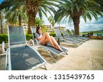 woman on a lounger by the pool... | Shutterstock . vector #1315439765