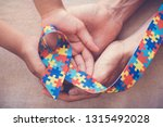 hands holding puzzle ribbon... | Shutterstock . vector #1315492028