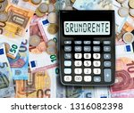 Small photo of German word GRUNDRENTE (basic pension) written on display of pocket calculator against cash money on table