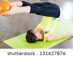 Pretty young girl fitness workout with small ball - stock photo