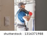 Caucasian Construction Worker with Heavy Duty Drill Driver. Industrial Theme. - stock photo