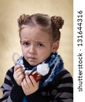 Little girl with the flu - holding cough medicine syrup and looking unhappy - stock photo