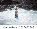 young boy looking at big waves... | Shutterstock . vector #1316681342