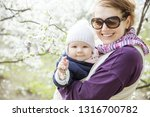 young woman carrying her baby... | Shutterstock . vector #1316700782