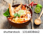 Stock photo tom yam kung prawn and lemon soup with mushrooms thai food in wooden bowl top view 1316838662