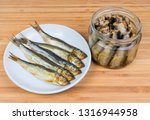 Stock photo smoked baltic herring on saucer and headless baltic herring preserved in vegetable oil in glass jar 1316944958