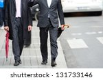 Anynomus men walking talking on sidewalk - stock photo