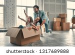 Small photo of Family on moving day. Attractive young woman and handsome bearded man with their cute little daughter are happy to move into new home.