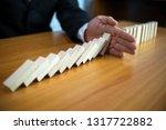 businessman hand stops domino... | Shutterstock . vector #1317722882