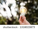hand holding light bulb with... | Shutterstock . vector #1318023875