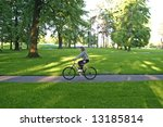 Girl cycling in city park on sunny day - stock photo