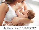 young woman breastfeeding her... | Shutterstock . vector #1318879742