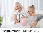 Little Girl Putting Money Into...