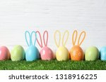 Stock photo set of colorful eggs with easter bunny ears on green grass against wooden background space for 1318916225