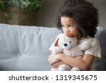 Small photo of Upset lonely bullied little african american kid girl holding teddy bear looking away feels abandoned abused, sad alone preschool mixed race child orphan hugging stuffed toy, charity adoption concept