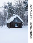 Small wooden forest house covered by snow - stock photo